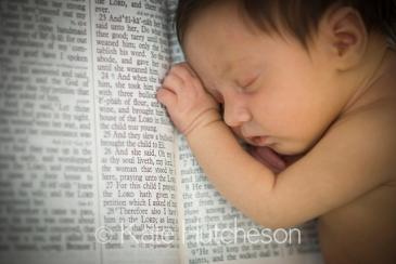 newborn baby sleeping on an open Bible