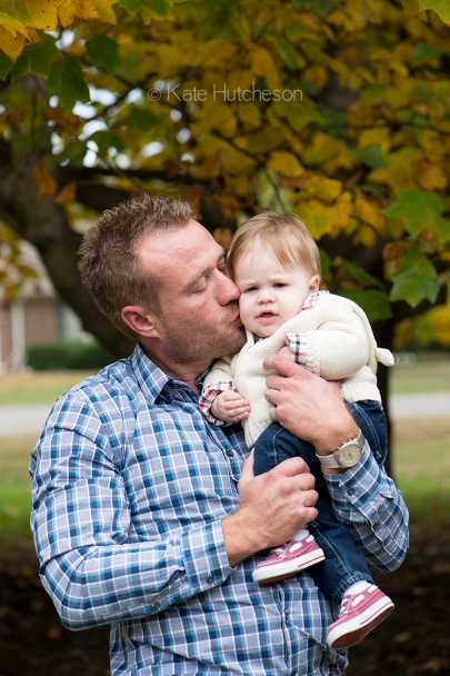 Daddy kissing baby outside