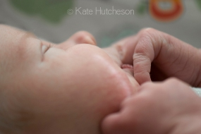 newborn sucking on his fingers